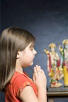 Side profile of a girl praying in front of statues of God Stock Photo - Premium Royalty-Freenull, Code: 630-01877580