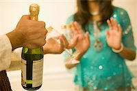 Close-up of a man's hand holding a champagne bottle Stock Photo - Premium Royalty-Freenull, Code: 630-01877716