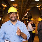 Worker in hardhat making thumbs up gesture Stock Photo - Premium Royalty-Freenull, Code: 604-01878333