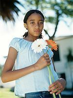 Girl (12-13) holding two flowers outdoors,portrait,waist up Stock Photo - Premium Royalty-Freenull, Code: 618-01882852
