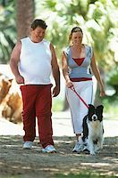 Mid adult couple in sportswear walking dog in park Stock Photo - Premium Royalty-Freenull, Code: 618-01884413