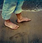 A man walking barefoot on the beach Stock Photo - Premium Royalty-Free, Artist: Jerzyworks, Code: 653-02001388