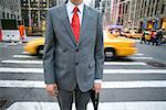 Midsection of a businessman standing in front of a pedestrian crossing Stock Photo - Premium Royalty-Free, Artist: ableimages, Code: 653-02001813