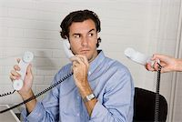 A businessman with three telephone receivers Stock Photo - Premium Royalty-Freenull, Code: 653-02001837