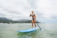 Woman on surfboard with paddle Stock Photo - Premium Royalty-Freenull, Code: 621-02027905