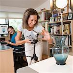 Mother and daughter preparing vase for auction Stock Photo - Premium Royalty-Free, Artist: Ikon Images, Code: 604-02043582