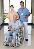 Two hospital workers in corridor with senior patient in wheelchair smiling Stock Photo - Premium Royalty-Freenull, Code: 635-02051409