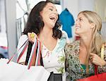 Two women in a store carrying shopping bags and laughing Stock Photo - Premium Royalty-Freenull, Code: 635-02051446