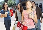 Four friends outdoors carrying shopping bags and smiling Stock Photo - Premium Royalty-Freenull, Code: 635-02051469