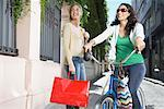 Two women outdoors with a bicycle and shopping bags smiling Stock Photo - Premium Royalty-Freenull, Code: 635-02051850