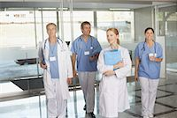 Four hospital workers walking in corridor holding clipboards and smiling Stock Photo - Premium Royalty-Freenull, Code: 635-02051945