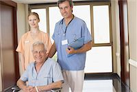 Two hospital workers in corridor with senior patient in wheelchair smiling Stock Photo - Premium Royalty-Freenull, Code: 635-02052028