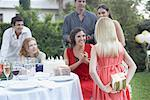 Young girl at outdoor birthday party about to give gift to woman with partygoers watching and smiling Stock Photo - Premium Royalty-Free, Artist: Masterfile, Code: 635-02052042