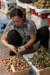 Woman Sorting Fruit at Market Stand, Ben Thanh Market, Ho Chi Minh City, Vietnam