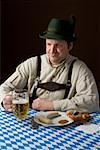 Stereotypical German man in Bavarian costume with a beer and German meal