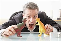 Businessman Playing with Toy Dinosaurs on Desk    Stock Photo - Premium Royalty-Freenull, Code: 600-02081699