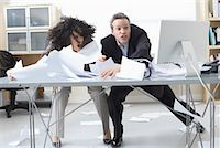 Business People Trying to Hold onto Paperwork Blowing Around on Desk    Stock Photo - Premium Royalty-Freenull, Code: 600-02081780
