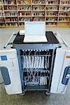 Cart of Laptops in Front of Bookshelves in School Library
