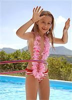 Young blonde girl with hula hoop and pink garland around neck by swimming pool    Stock Photo - Premium Rights-Managednull, Code: 822-02124379