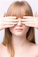 Portrait of young woman covering eyes with hands    Stock Photo - Premium Rights-Managednull, Code: 822-02125048