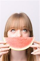 Close up of young woman covering mouth with slice of water melon    Stock Photo - Premium Rights-Managednull, Code: 822-02125050