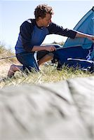 Portrait of young man crouching and erecting tent    Stock Photo - Premium Rights-Managednull, Code: 822-02136703