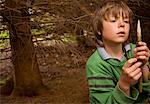 Portrait of young boy sharpening a wooden stick in a campsite    Stock Photo - Premium Rights-Managed, Artist: ableimages, Code: 822-02137204