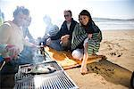 Group of friends sitting around a barbeque on the beach    Stock Photo - Premium Rights-Managed, Artist: ableimages, Code: 822-02137441