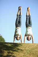 Twin Caucasian teenage girls perform side by side handstands in the park. Stock Photo - Premium Royalty-Freenull, Code: 673-02137860
