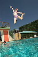 Girl leaping into a swimming pool. Stock Photo - Premium Royalty-Freenull, Code: 673-02137944