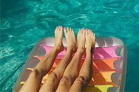 Two pairs of girls' legs on a raft. Stock Photo - Premium Royalty-Freenull, Code: 673-02138196