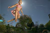 Young girl jumping into a pool. Stock Photo - Premium Royalty-Freenull, Code: 673-02138200