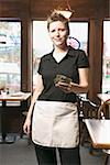 Young waitress holding out money. Stock Photo - Premium Royalty-Free, Artist: AlaskaStock, Code: 673-02138595