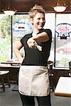 Young waitress holding out money. Stock Photo - Premium Royalty-Free, Artist: Ikon Images, Code: 673-02138596
