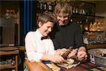 Two restaurant workers counting cash on the bar top. Stock Photo - Premium Royalty-Free, Artist: AlaskaStock, Code: 673-02138601