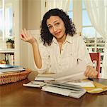 Exasperated woman working on a stack of bills. Stock Photo - Premium Royalty-Free, Artist: Ikon Images, Code: 673-02138614