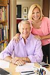 Portrait of a middleaged couple in their home office paying bills. Stock Photo - Premium Royalty-Free, Artist: AlaskaStock, Code: 673-02138646