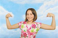 A teenaged girl flexing her muscles Stock Photo - Premium Royalty-Freenull, Code: 673-02138881
