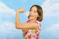 A teenaged girl flexing her muscles Stock Photo - Premium Royalty-Freenull, Code: 673-02138882