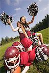 Cheerleaders sitting on football players
