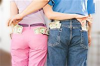 Couple sneaking money from each other Stock Photo - Premium Royalty-Freenull, Code: 673-02139330