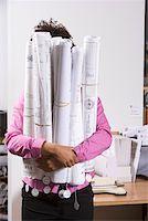 Woman holding bundle of blueprints Stock Photo - Premium Royalty-Freenull, Code: 673-02139708