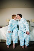 Couple in matching pajamas kissing Stock Photo - Premium Royalty-Freenull, Code: 673-02140410