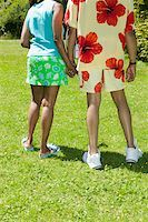 Couple holding hands on sunny lawn Stock Photo - Premium Royalty-Freenull, Code: 673-02140449