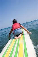 Young girl paddling surfboard Stock Photo - Premium Royalty-Freenull, Code: 673-02140740
