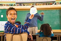Boy holding drawing over teacher's face Stock Photo - Premium Royalty-Freenull, Code: 673-02141911