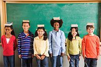 Row of students with books on their heads in classroom Stock Photo - Premium Royalty-Freenull, Code: 673-02141922