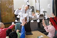 Businesspeople throwing paper at meeting Stock Photo - Premium Royalty-Freenull, Code: 673-02142279