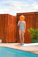 Girl with balloon in front of face over swimming pool Stock Photo - Premium Royalty-Freenull, Code: 673-02143229