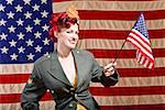Woman wearing military jacket and holding American flag